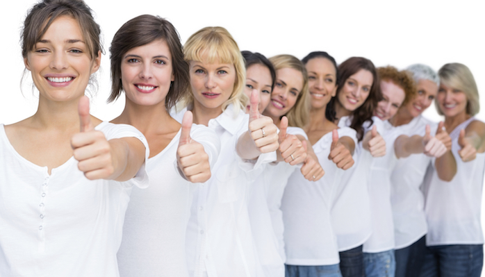 Cheerful casual models posing in a line thumbs up on white background